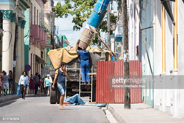 Cuban construction workers using a rubble chute made with day to day objects like oil drums wooden boards