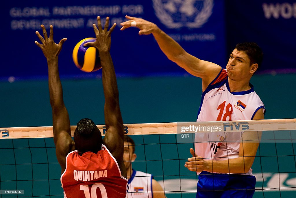 Cuban Danger Jorber Quintana tries to block a spike by Serbian player Marko Podrascanin during their World League volleyball tournament match on June...