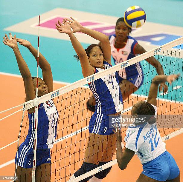 Cuban defenders Daimi Ramirez Echevarria and Rachel Sanchez Perez jump to block a spike by Italy's Taismary Aguero during the women's World Cup...