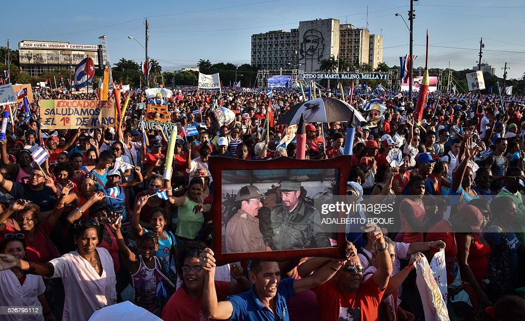 A Cuban displays a picture showing Cuban former president Fidel Castro (R) and president Raul Castro during the May Day parade in Havana, on May 1, 2016. / AFP / ADALBERTO