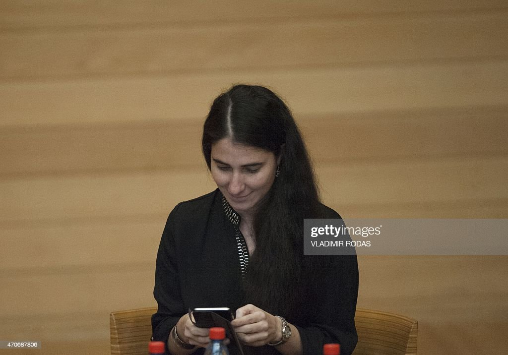 Cuban dissident blogger Yoani Sanchez checks her mobile phone before giving a speech at the Adolfo Ibañez University in Santiago, Chile, on April 22, 2015. Sanchez gave her perspective about Cuba and talked about her life as a blogger. AFP PHOTO / Vladimir Rodas