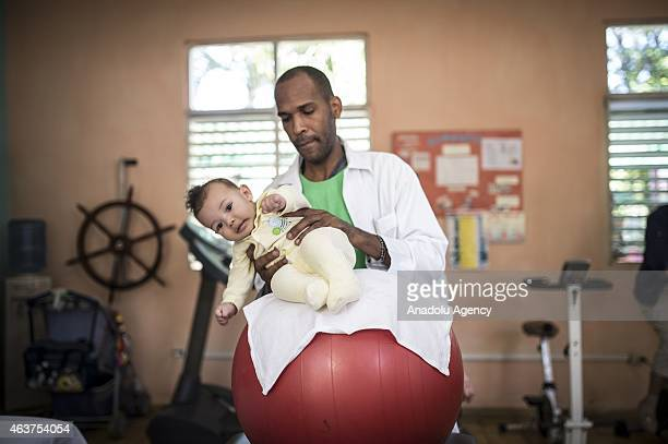 Cuban doctors holds a baby at '19 De Abril' hospital in Havana Cuba on February 12 2015 A Cuban family physician typically spends the morning seeing...