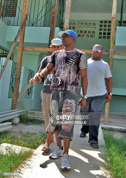 Cuban double Olympic and world bantamweight champion Guillermo Rigondeaux walks with friends in the front of his house in Havana 08 August 2007...