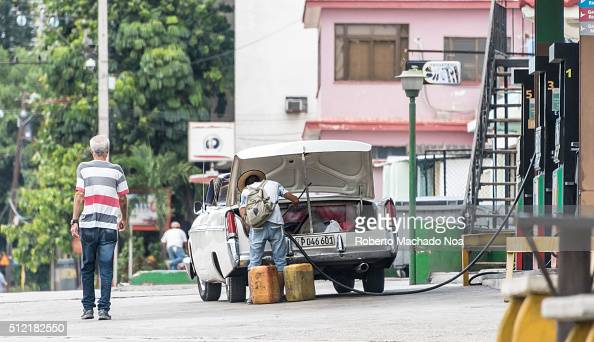 Cuban driver putting gasoline can in the back of car He is trying to transporting gasoline by car The practice is prohibited but goes unnoticed by...