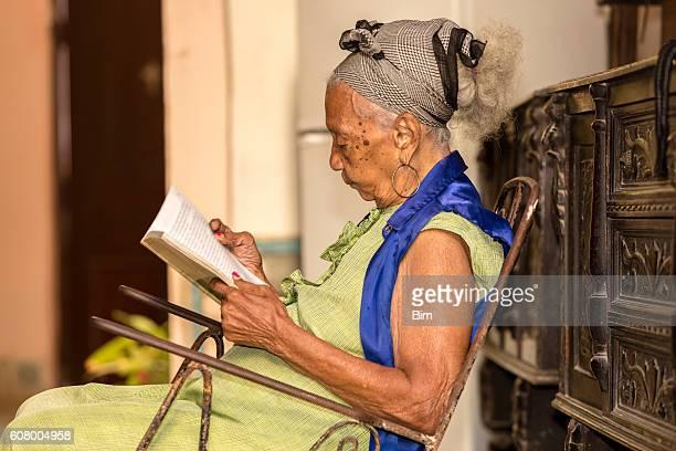 Cuban elderly woman reading a book