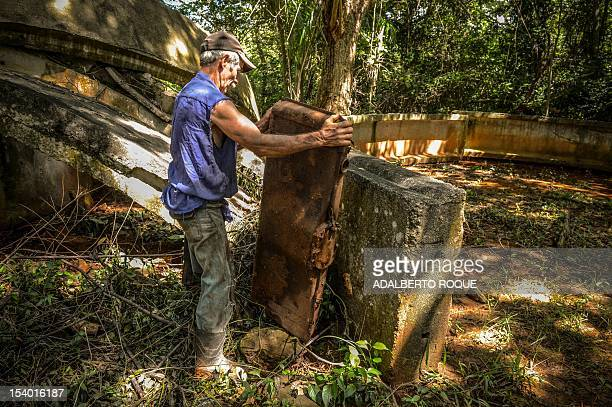 Cuban farmer Jose Teston moves a fuel tank used by a vehicle during the 1962 missile crisis at the site of a Russian R12 theatre missile silo in San...