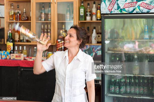 Cuban female bartender in tourist hotel and juggling with the Havana Club rum bottle