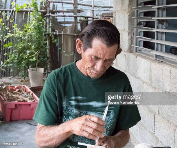 Cuban fisherman knitting a fishing net Old man with wrinkled face in green Tee standing near stoned wall in small village house