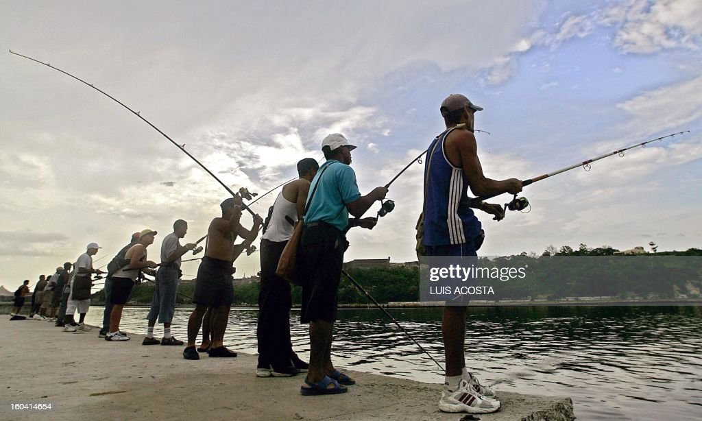 Cuban fishermen dip their baits 21 June, 2005 from Havana's Malecon (seafront). Every day, dozens of fishermen gather around Havana's bay in the hope of a good fishing that helps them to subsist. AFP PHOTO/Luis ACOSTA /