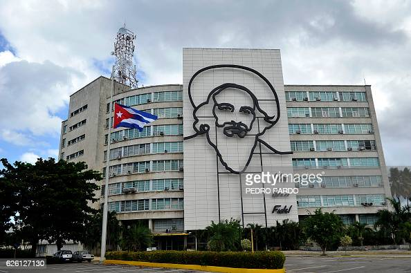 A Cuban flag flutters at half mast near an image of revolutionary Camilo Cienfuegos following the death of Cuban revolutionary leader Fidel Castro at...