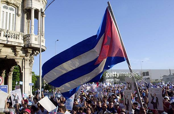 Cuban flag is flown by a demonstrator in front of the Spanish Embassy as thousands march in the streets after the Cuban government's call to protest...