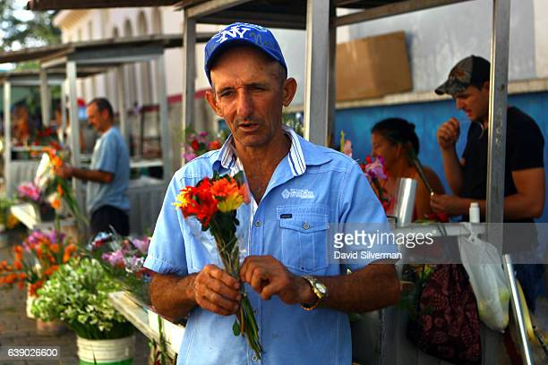 Cuban florist prepares a bouquet of flowers on December 24 2015 at ab outdoor market in Santa Clara Cuba Many Cuban vendors rely on the income from...