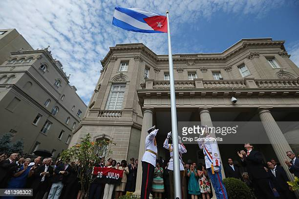 Cuban Foreign Minister Bruno Rodriguez applauds as the Cuban flag is raised in front of the country's embassy for the first time in 54 years July 20...