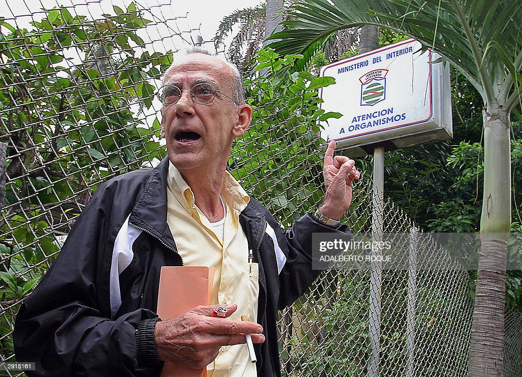Cuban former major, Eloy Gutierrez Menoyo, points out at a sign of the Immigration office in Havana, 30 January 2004, where he arrived to demand the regularization of his migration papers, expired 6 months ago, when Menoyo refused to fly back to Miami after spending his holidays in the island. The dissident stayed in the country with the intention of having an interview with Cuban President Fidel Castro and ask for his permission to form an opposition party. AFP PHOTO/Adalberto ROQUE