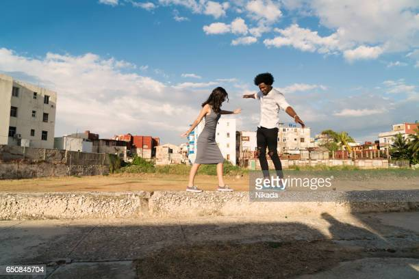 cuban friends balancing on retaining wall at park against cloudy sky