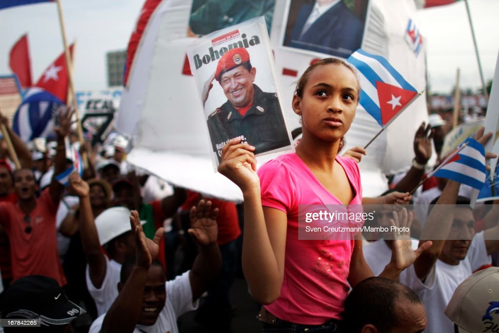 A Cuban girl holds up a photo of the late Venezuelan President Hugo Chavez, during the annual May Day parade of hundreds of Cubans at the Revolution square on May 1, 2013, in Havana, Cuba. Fidel Castro last attended a May Day parade in 2006, before he fell ill, just two months later.