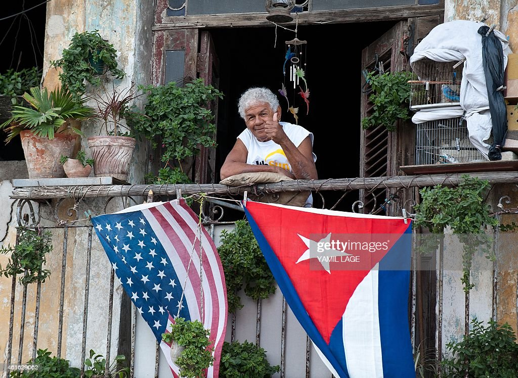 A Cuban gives the thumbs up from his balcony decorated with the US and Cuban flags in Havana on January 16 2015 The United States will ease travel...