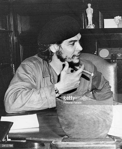 Cuban guerrilla revoutionary leader Ernesto 'Che' Guevara sits at a desk holding a cigar late 1950s