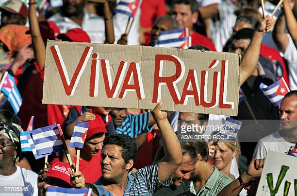 Cuban holds a sign cheering acting President Raul Castro 02 December 2006 at Revolution Square in Havana during a military parade celebrating...