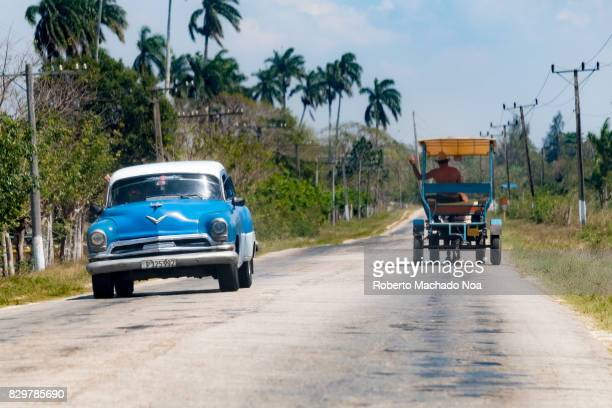 Cuban horse drawn cart passes an old American car in the road After the economic issues of the Caribbean island the use of animal drawn vehicles for...