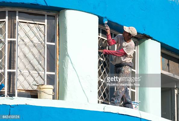 Cuban house painter in old building exterior He has no safety or protective gear as he works in a window