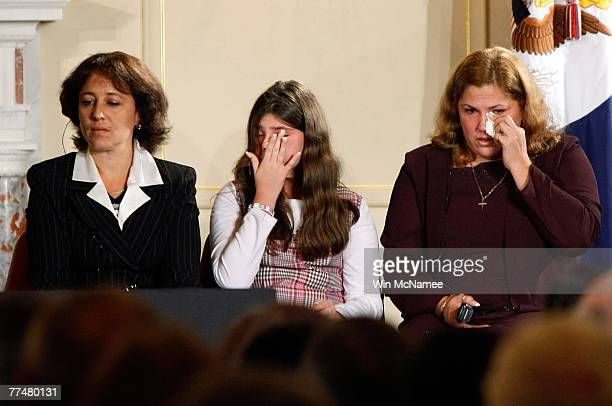 Cuban immigrants to the US Ms Yamile Llanes Labrada Miss Melissa Gonzalez and Mrs Marlenis Gonzalez listen as US President George W Bush speaks on...
