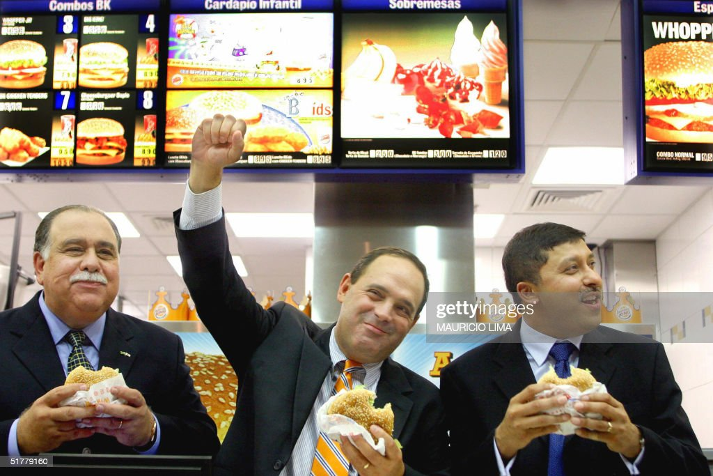 Cuban Julio Ramirez (C), chairman of Burger King for Latin America and the Caribbean, gestures while eating a hamburger alongside Indian Nish Kankiwala (R), chairman of Burger King International Corporation and Brazilian Luiz Eduardo Batalha (L), chairman of BGK do Brasil -an investors' consortium group which will operate the Burger King in Brazil- during the launching of their first fast food restaurant 23 November, 2004 in Sao Paulo, Brazil. Second largest burger restaurant chain worldwide, U.S. Burger King announced its first franchised restaurant of 50 restaurants planned for Sao Paulo State in the next five years, creating approximately 3.000 direct new jobs with investment around U$ 20 million dollars. AFP PHOTO/Mauricio LIMA