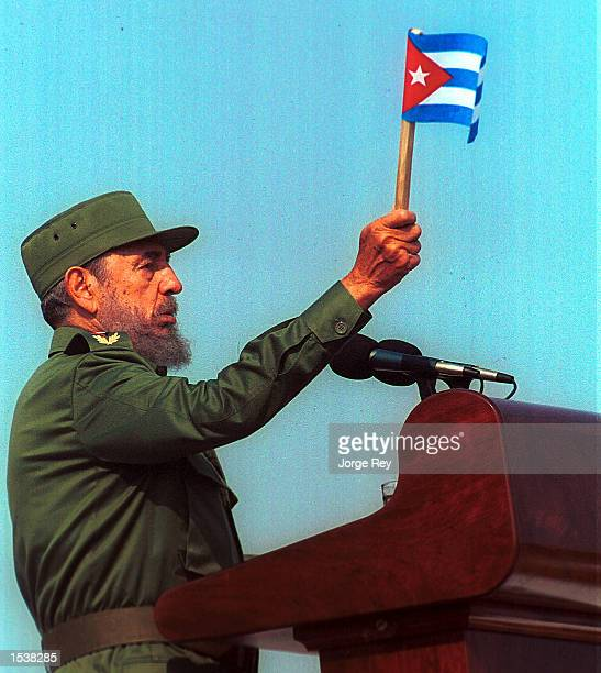 Cuban leader Fidel Castro waves a flag while he speaks May 1 2002 during a celebration of May Day at the Revolution Plaza of Havana Cuba Thousands...
