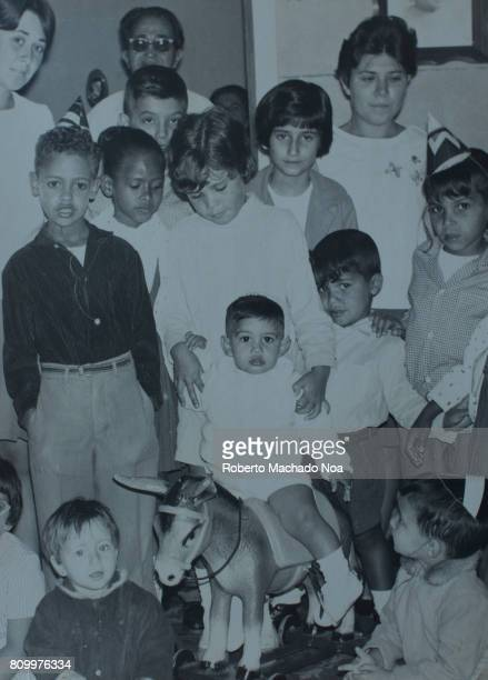 Cuban lifestyle in 1968 First Year Birthday Celebration Old black and white photo of kids with the youngest one riding a toy horse