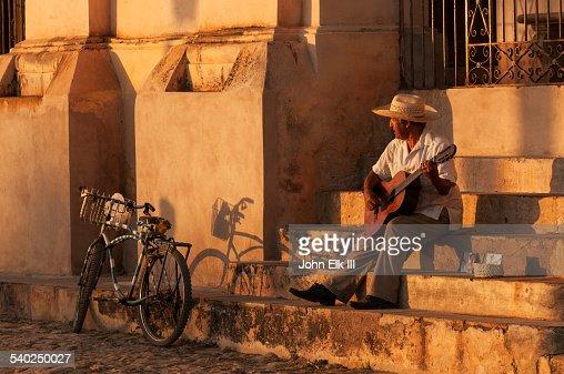 Cuban man on steps playing guitar