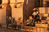 Cuban man on steps playing guitar