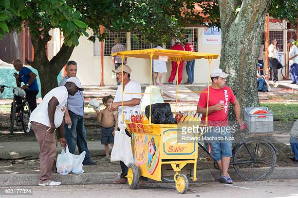 Cuban man selling a drink of flavored crushed ice or slush during the hot summer months After the reforms of the Raul Castro government many go to...