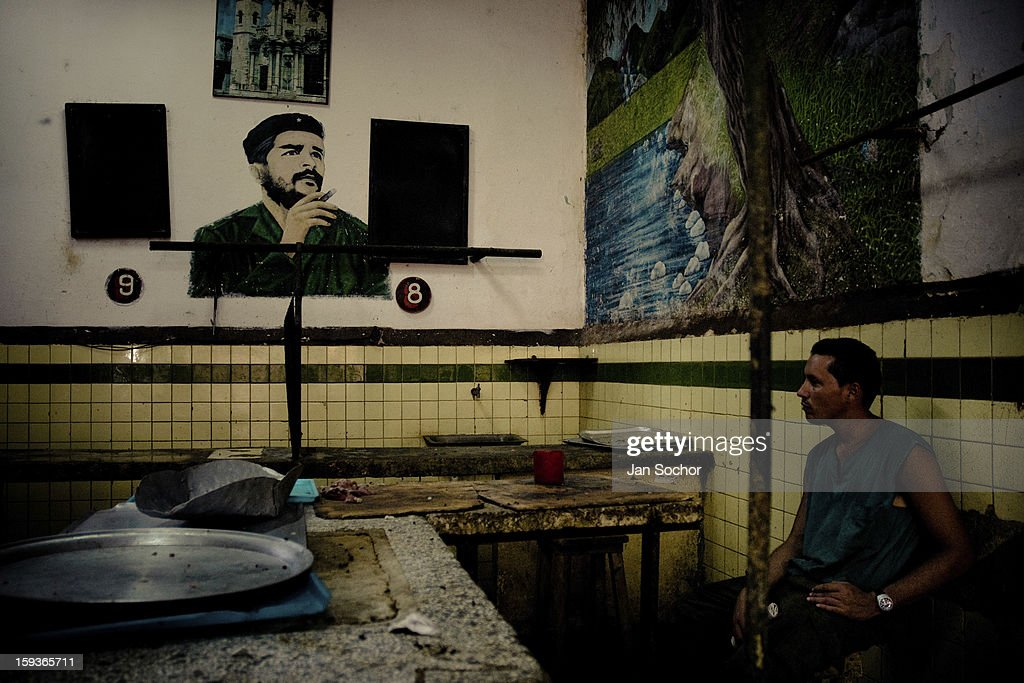 A Cuban man stands in front of a portrait of the revolutionary leader Che Guevara, hung on the wall of a vegetable market, in Havana, Cuba, 16 August 2008 in Havana, Cuba. During the Cuban Revolution, an armed rebellion at the end of the 1950s, most of the revolutionary leaders started as unnamed soldiers fighting from the jungle. After taking over the power, they became autocratic rulers holding almost absolute power and pursuing the opposition. For some reason Cuban people never stopped to worship Fidel Castro, Che Guevara, Raul Castro and others. Cubans hang their photos and portraits on the wall at home, shops and working places even when they don't have to.