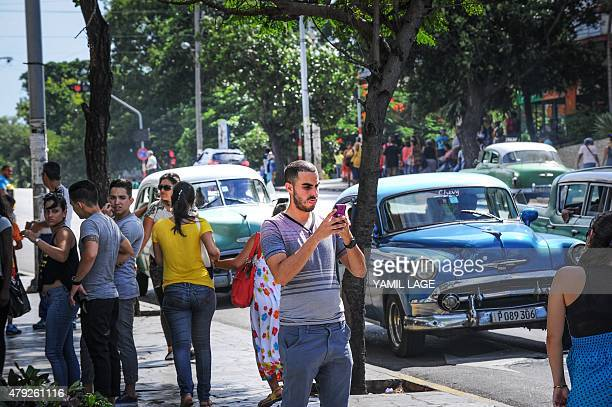 A Cuban man takes a picture with his mobile phone in a street of Havana on July 2 2015 Cuban stateowned telecommunications company Etecsa opened 35...