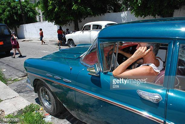 A Cuban man uses his mobile phone on a car on May 26 2010 in Havana AFP PHOTO/STR