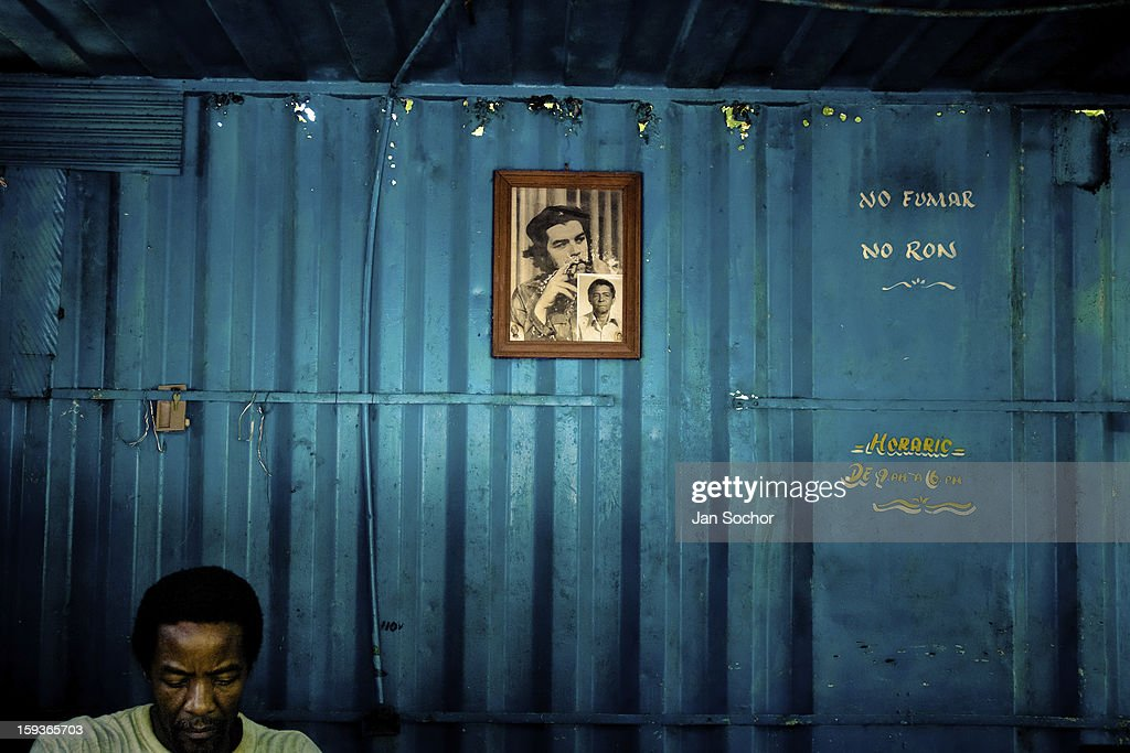 A Cuban man works in front of a portrait of the revolutionary leader Che Guevara, hung on the wall of a movable locksmithery in Alamar (the Eastern Havana), Cuba, 14 August 2008 in Havana, Cuba. During the Cuban Revolution, an armed rebellion at the end of the 1950s, most of the revolutionary leaders started as unnamed soldiers fighting from the jungle. After taking over the power, they became autocratic rulers holding almost absolute power and pursuing the opposition. For some reason Cuban people never stopped to worship Fidel Castro, Che Guevara, Raul Castro and others. Cubans hang their photos and portraits on the wall at home, shops and working places even when they don't have to.