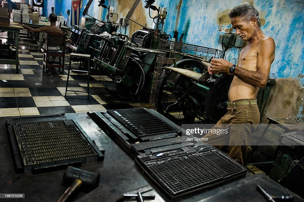 A Cuban master printer, leant against a printing machine, waits for a new load in the state print shop, Santiago de Cuba, Cuba, 4 August 2008.