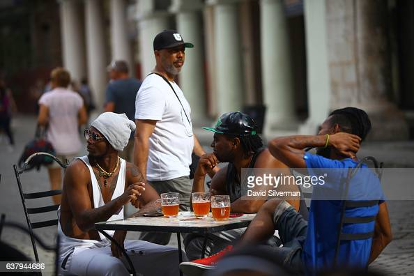 Cuban men take a table at the Factoria Plaza Vieja microbrewery and restaurant on December 22 2015 in Havana Cuba The joint CubanAustrian venture...