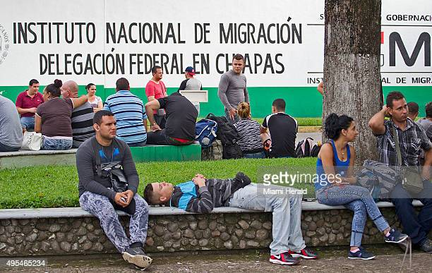 Cuban migrants wait to be processed outside the Mexican National Institute of Migration shortly after they had crossed the Rio Suchate the body of...