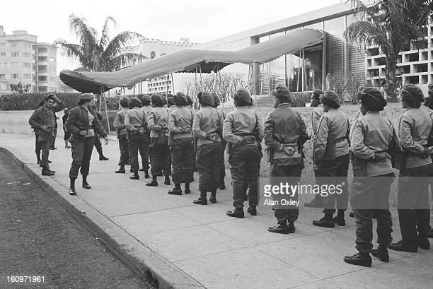 Cuban militia girls strut outside the American Embassy in Havana in January 1961 as Washington cuts relations and diplomats evacuate the building...