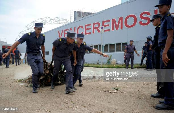 Cuban Navy personnel collect garbage and debris during the cleanup ensuing the passage of Hurricane Irma in Havana on September 12 2017 / AFP PHOTO /...