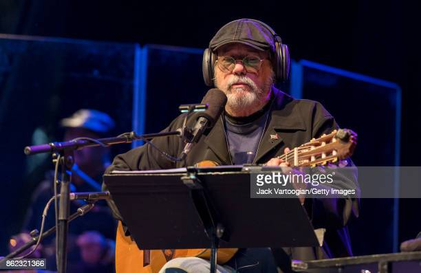 Cuban Nueva Trova musician Silvio Rodriguez plays guitar as he performs during a benefit for SummerStage at Central Park SummerStage New York New...