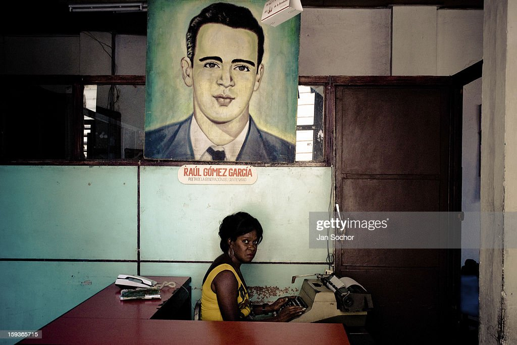 A Cuban office worker types under a painted portrait of the revolutionary leader and poet Raul Gomez Garcia, hung on the wall of the Cuban state office in Santiago de Cuba, Cuba, 5 August 2008 in Havana, Cuba. During the Cuban Revolution, an armed rebellion at the end of the 1950s, most of the revolutionary leaders started as unnamed soldiers fighting from the jungle. After taking over the power, they became autocratic rulers holding almost absolute power and pursuing the opposition. For some reason Cuban people never stopped to worship Fidel Castro, Che Guevara, Raul Castro and others. Cubans hang their photos and portraits on the wall at home, shops and working places even when they don't have to.