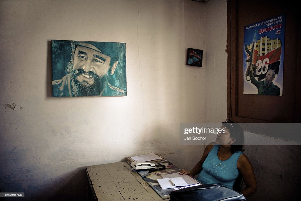 A Cuban office worker watching a painted portrait of the Cuban Revolutionary leader Fidel Castro, hung on the wall of the Cuban state office in Santiago de Cuba, Cuba, 31 July 2008 in Havana, Cuba. During the Cuban Revolution, an armed rebellion at the end of the 1950s, most of the revolutionary leaders started as unnamed soldiers fighting from the jungle. After taking over the power, they became autocratic rulers holding almost absolute power and pursuing the opposition. For some reason Cuban people never stopped to worship Fidel Castro, Che Guevara, Raul Castro and others. Cubans hang their photos and portraits on the wall at home, shops and working places even when they don't have to.