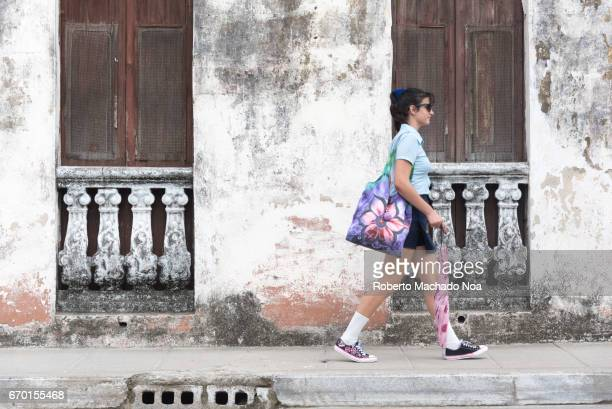 Cuban old weathered and worn out architecture Cuban female student passing in front of old house Results of economic hardship on real estate