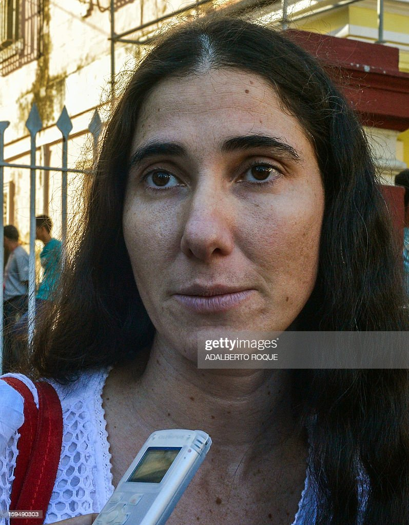 Cuban opposition blogger Yoani Sanchez listens to a question from a journalist outside a Migration Office, on January 14, 2013 in Havana