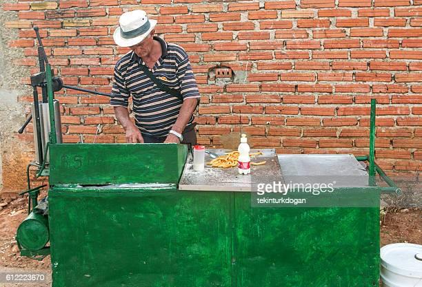 cuban person selling street food churro at trinidad cuba