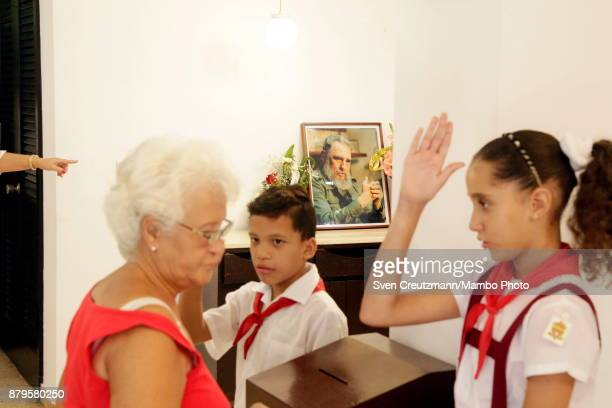 Cuban pioneers salute after a woman cast her vote in the place where Revolution leader Fidel Castro used to cast his vote on occasion of municipal...
