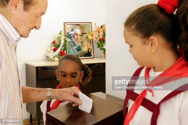 Cuban pioneers watch as a man casts his vote in the place where Revolution leader Fidel Castro used to cast his vote on occasion of municipal...