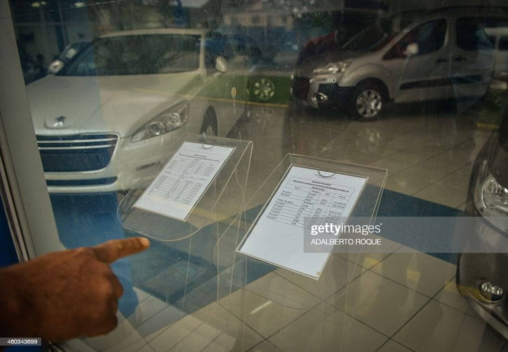 A Cuban points at the listed prices list of new and used foreign-made cars for sale at a car dealer in Havana on January 3, 2014. The free sale of cars in Cuba has been officially authorized Friday, but at astronomical prices.